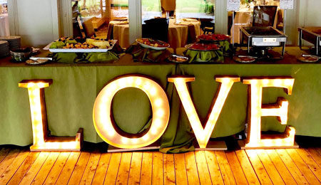 Love sign in front of a buffet at an engagement party